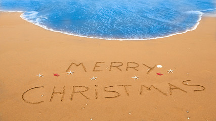merry christmas written on a sandy beach near the surf