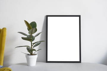 Poster A2 in black frame in nordic stylish modern interior, yellow armchair, ficus, living room. Empty space for design layout..