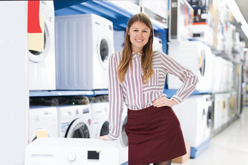 smiling saleswoman offering clothes washer