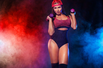 Attractive young fitness woman athlete and bodybuilder holding dumbbell on black background with color smoke. Copy space for fitness nutrition ads.
