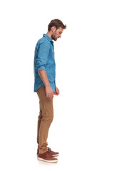 side view of a casual man looking down at something