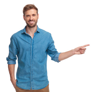 smiling young man is pointing to side