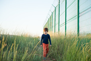 one little boy refugee walking along high fence with razor wire news report