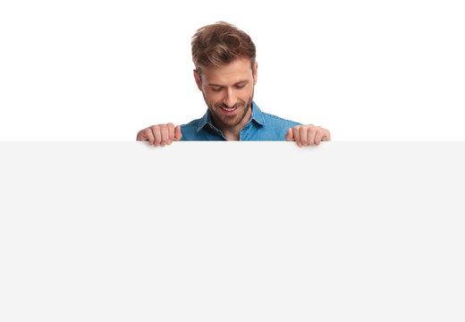 smiling casual man holding blank board looks down at it