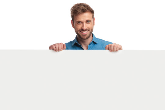 smiling young casual man presenting a blank board