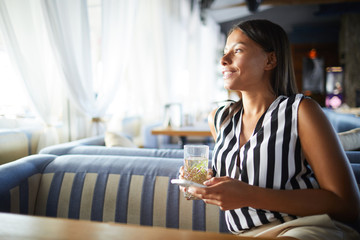Young relaxed woman sitting in cafe, having drink and communicating through messages in smartphone