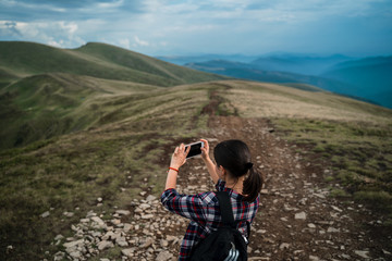 Tourist is taking photo of amazing view on cell phone. Carpathians, Ukraine