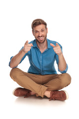 happy man sitting on the floor is pointing his fingers