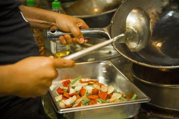 Hands of cook preparing roast with salad