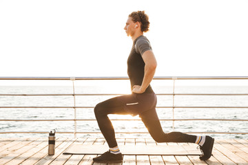 Portrait of a healthy sportsman doing lunges exercises