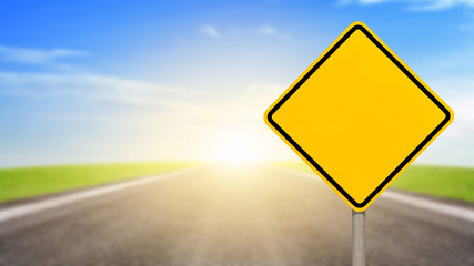 Blank yellow road sign or Empty traffic signs on blurred asphalt road with colorful light background. Concept of success in the future goal
