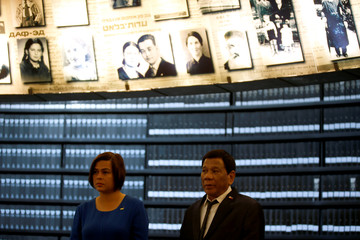 Philippine President Rodrigo Duterte stands beneath pictures of Jews killed in the Holocaust during a visit to the Hall of Names at Yad Vashem's Holocaust History Museum in Jerusalem