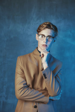 Studio portrait of young male model with red hair and freckles. Weared in brown coat and glasses. Blue light and background.