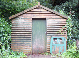 An old wooden shed with a green painted door and discarded gate leaning on the wall surrounded by trees and woodland with weeds growing on the ground