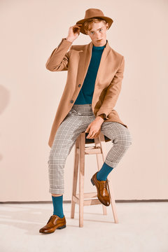 Young male model with red hair and freckles posing in brown coat and hat, plaid pants, turquoise sweater and socks, brown shoes, sitting on chair. Pink background