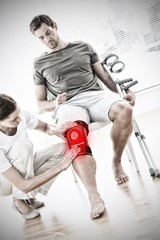 Composite image of physiotherapist checking man with crutches