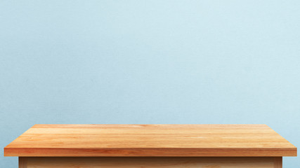 Empty wooden tabletop isolated on blue wall background. For your product placement or montage with focus to the table top in the foreground. Empty pine wooden shelf. shelves