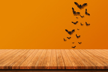 Empty wooden tabletop isolated on orange background. Bats flying made from wood on orange brick...