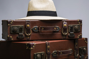 Close-up of straw hat on old suitcase. Old suitcase for traveling
