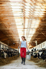 Full length portrait of modern young woman  holding buckets walking towards camera in sunlit cow shed, copy space