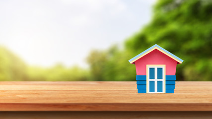 House model on wooden table up over blurred nature background. Investment and saving concept