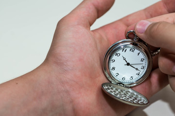 Caucasian male hand adjusting the pocket watch, conceptual image of   daylight savings time.