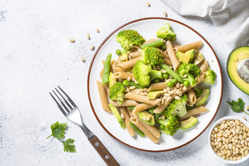 Vegan pasta penne with broccoli, avocado and pine nuts top view.