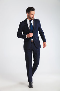 young businessman walking and buttoning his navy suit