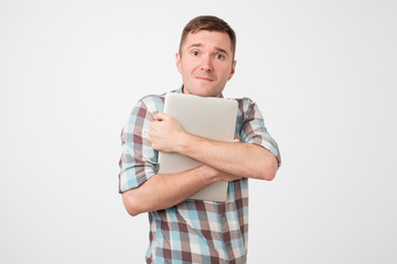 Portrait of confident young man laptop standing against blue wall