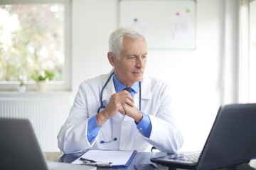Senior male doctor working at consulting room