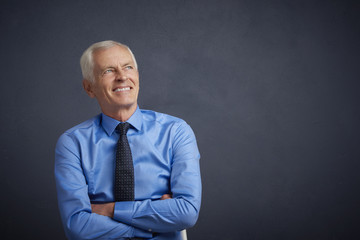 Senior man portrait. Shot of an elderly businessman wearing suit and looking up while standing at grey background.