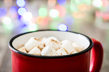 Christmas cocoa with marshmallow and Christmas lights background on wooden table