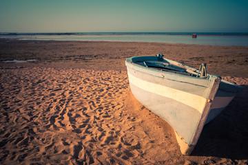 Tropical Seascape with a fishing boat on beach on warm sunset, Sri Lanka. Beach. Sun and Sand.