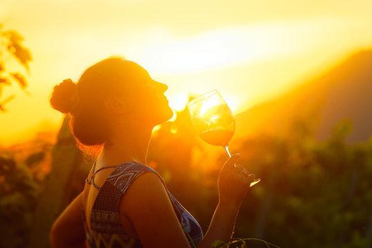 Portrait of woman in the vineyard having wine