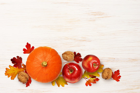 Round pumpkin, apples and walnuts with colorful leaves on wood