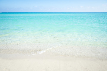 Calm clear tropical turquoise water lap at a white sandy beach