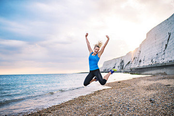 Young sporty woman runner in blue sportswear jumping on the beach outside.