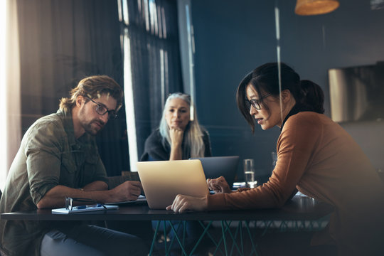 Woman sharing her ideas with laptop to colleagues