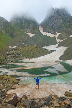 Partially frozen Didighali lake with a young man and mountain pass in the background in Caucasus mountains on a hiking trail to Silver Lakes in Georgia