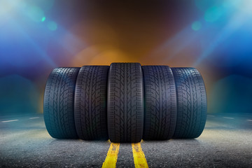 Five car tires standing on a road with red and blue lights at background