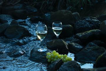 Weißwein und Weintrauben Steinen im Wasser. Farben im kühlen Blau
