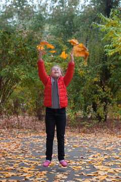 A girl with special needs jumping on a background of autumn forest