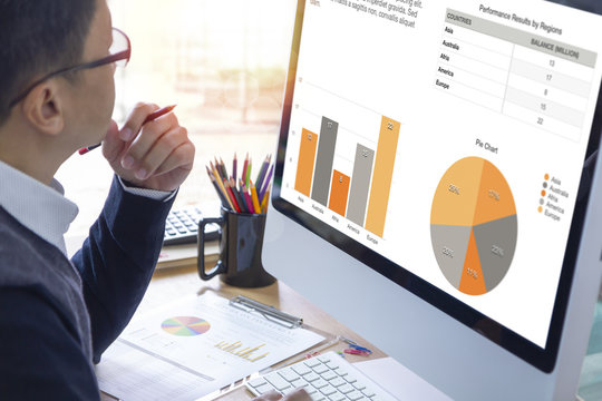Businessman looking into a modern computer screen reviewing a business performance with colorful graphs.