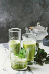 Matcha green tea iced latte or cocktail in three different glasses with ice cubes, matcha powder and jug of milk on white marble table, decorated by green branches. Grey wall at background