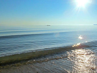 Landscape with water, sun with bright sunbeams in the sky and a boat on skyline. Beautiful view of Lake Huron, the Great Lakes region, USA.
