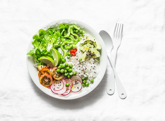 Coconut rice and vegetables buddha bowl. Vegetarian healthy lunch - rice, salad, avocado, radish, tomatoes on a light background, top view