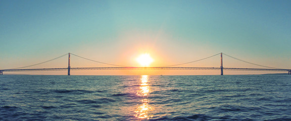 Mackinac Bridge in Michigan at sunset. Horizontal panoramic view of a long steel suspension bridge located in the Great lakes region of North America.
