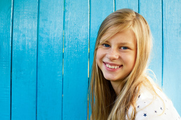 Portrait of a beautiful blond teenage girl on a blue wall background
