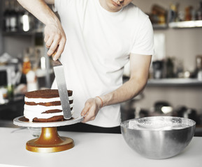 Close up of young man smearing cream on chocolate cake by metal spatula in hand.