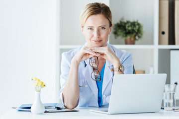 smiling female doctor in eyeglasses looking at camera at table with laptop in office